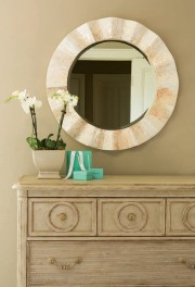 The weathered birch-finished bureau from Stanley (bottom) helps lighten the room, while the capiz shell mirror helps reflect light.