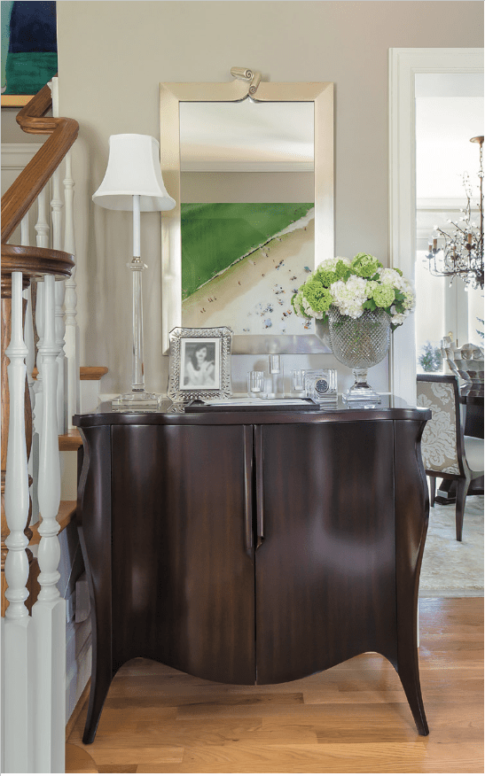 Next to the stairway in the entry, a Christopher Guy cabinet and mirror and a crystal Visual Comfort & Co. lamp create a striking vignette to greet visitors.