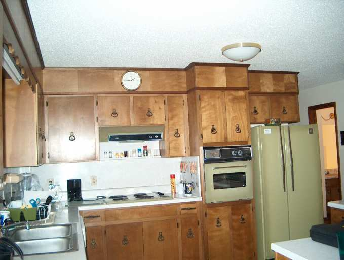 Before - Outdate Kitchen Lots of cabinet space but dark stained cabinets and avocado color appliances make this kitchen dated.