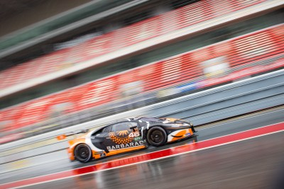 An orange and black Lambourghini Huracan moves down a rain soaked pit lane in the rain against a motion blurred background of red and grey parallel lines of colour. VdeV Endurance Series, Circuit de Barcelona-Catalunya, March 2018
