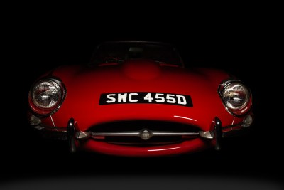 Low front end view of a red 1966 Series 1 E-Type Jaguar 4.2 coming out of the shadows