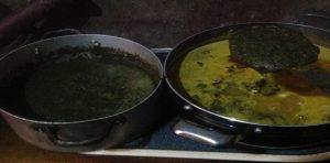 Adding the blended leaves to the palm sauce after adding the meat and all other condiments
