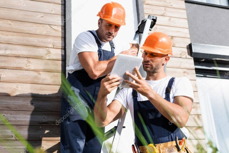 Selective focus of builders using digital tablet near ladder and facade of house