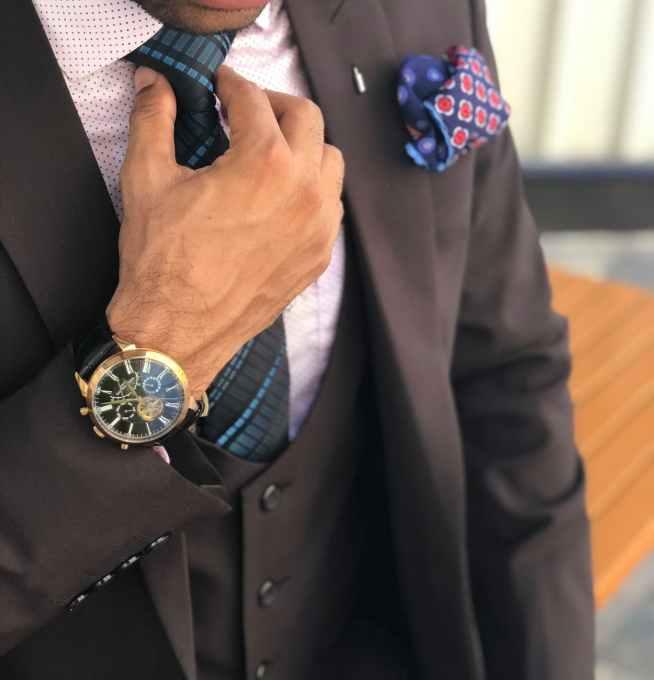 man in formal suit jacket holding his necktie