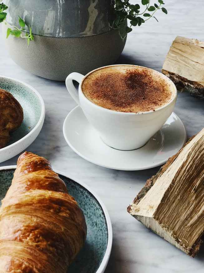 cup of coffee near croissant bread
