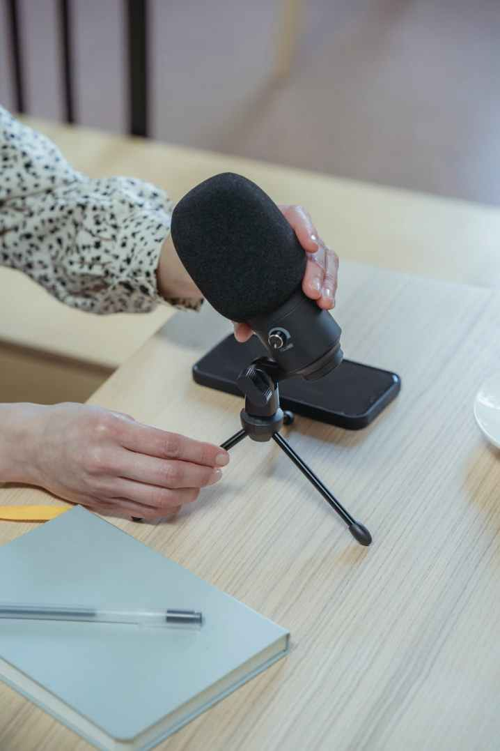 anonymous woman putting microphone on table before conference in office