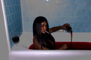 girl pouring wine into bath tub