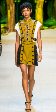 DOLCE & GABBANA The embellished military style is present in the mustard colored halter top and matching mini skirt. The white t-shirt underneath the halter adds to the uniformed component of the design; however, the fringed strappy sandals create a more casual style.