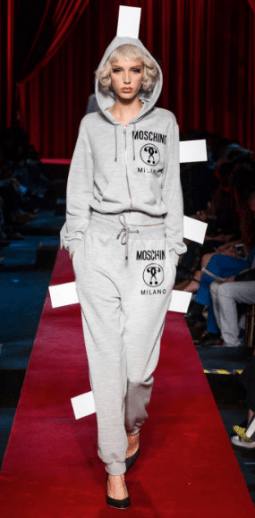 "MOSHINO The street style sweatpants design promotes the brand ""Moschino"" on both the sweatshirt and pants. The high heels are not ""too much"" as the clothing itself is only a subtle gray."