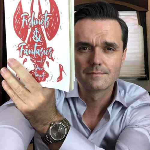 Dark-haired actor holding up book
