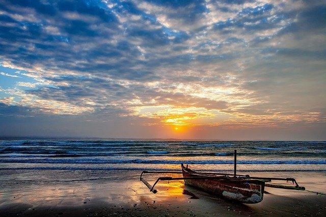 朝日の岸部と小船