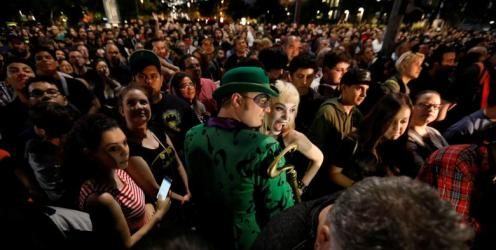 A person dressed as the Riddler poses for a photo as a bat-signal is projected on City Hall in honor of late actor Adam West in Los Angeles