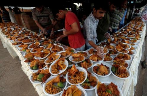 Men arrange food plates for passersby to break their fast during a Muslim holy month of Ramadan in Karachi
