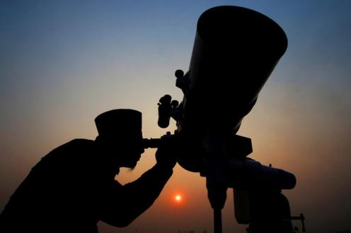 An official looks through a telescope for the sighting of the new moon for the start of the Muslim fasting month of Ramadan at a religious boarding school in Jakarta