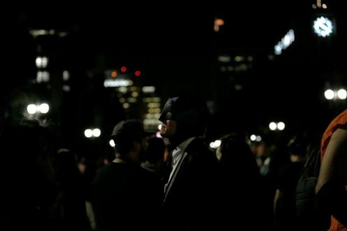 A person wearing a Batman costume watches as a bat-signal is projected on City Hall in honor of late actor Adam West in Los Angeles