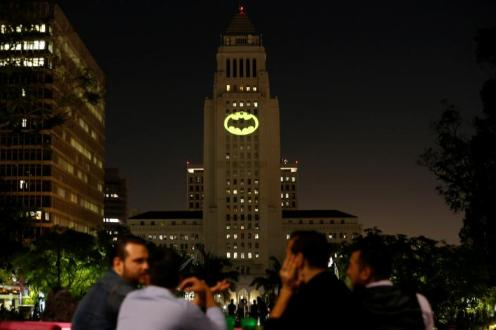 People watch as a bat-signal is projected on City Hall in honor of late actor Adam West in Los Angeles