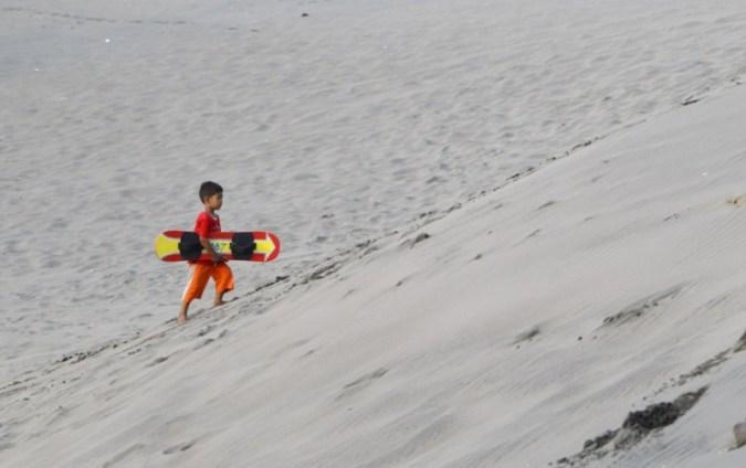 Anak kecil pegang papan sandboarding di Jogja