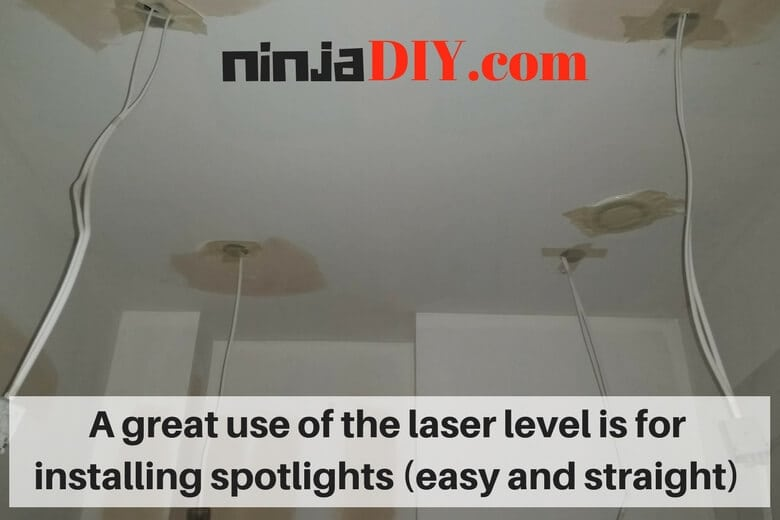 ceiling works installing spotlights using a laser level for electricians