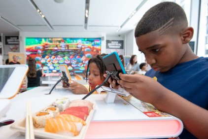 In this photo provided by Nintendo of America, Tristan W, age 7, from Queens, NY, and Isaiah M., age 7, from Queens, NY, celebrate International Sushi Day by playing the new Sushi Striker: The Way of Sushido game during a special event at the Nintendo NY store in Rockefeller Plaza. An action-packed puzzle game thatÕs all about matching plates and eating sushi, Sushi Striker: The Way of Sushido is now available for the Nintendo Switch system and in 2D for the Nintendo 3DS family of systems. A free demo is also available in Nintendo eShop on Nintendo Switch Ð perfect for International Sushi Day on June 18!