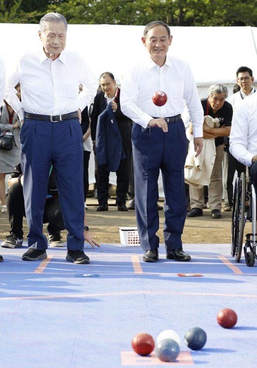 سوغا (يمين) يُجرب رياضة البوكا عام 2019 برفقة يوشيرو موري (يسار) رئيس الوزراء الأسبق، ترويجاً لألعاب طوكيو البارلمبية 2020 | عبر مكتب رئيس الوزراء الياباني وكيودو