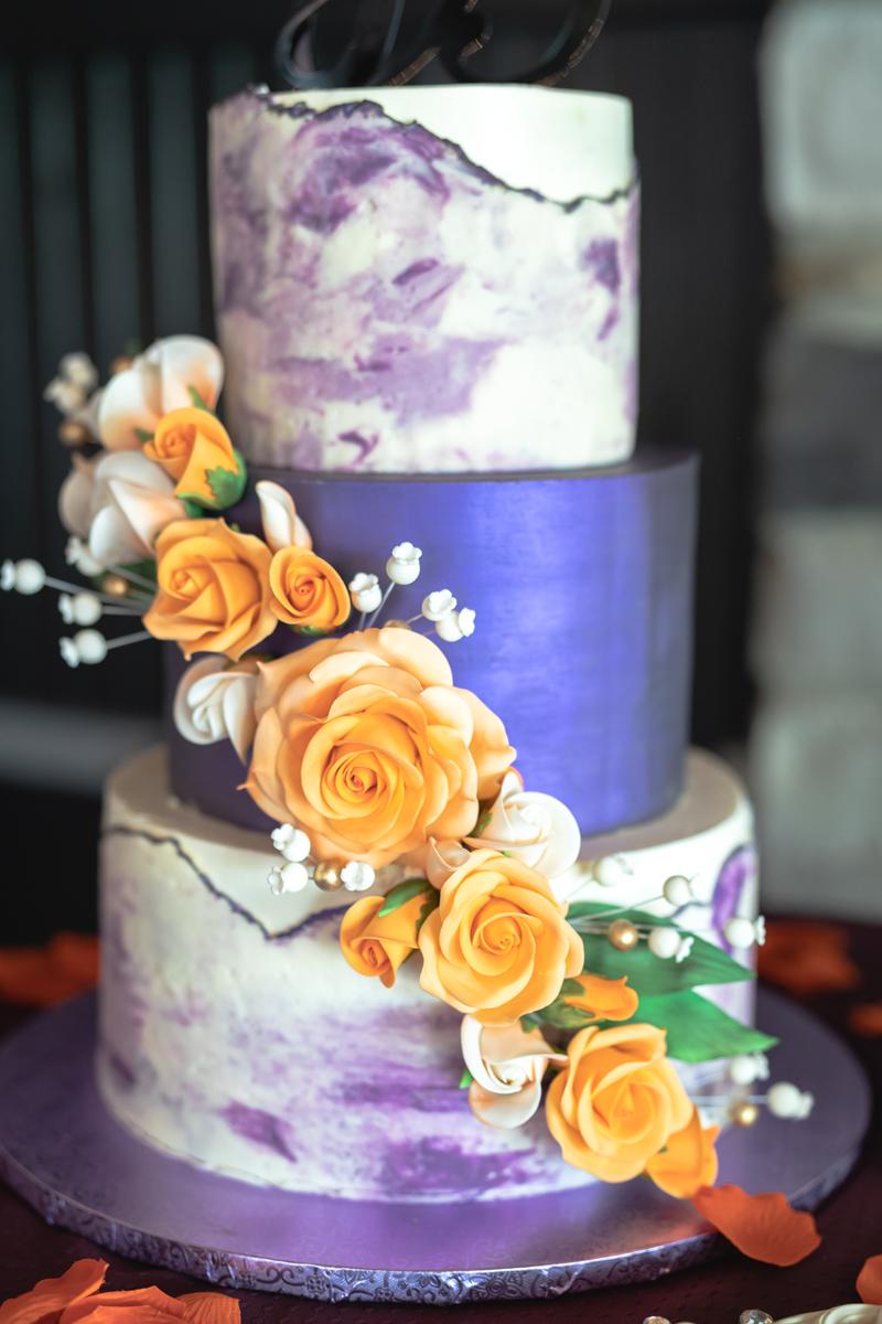 Purple, white and orange three tiered wedding cake to celebrate Jennifer and Bea's nuptials.