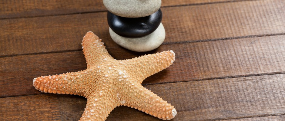 Pebble stones with star fish on a table