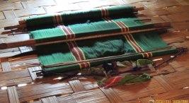 রুনাজন পাড়ায় যার ঘরে খেলাম, তার ঘরের ঘরণী কোমর তাতে কাপড় বুনছিলেন, মেঝেতে রাখা দেখলাম। (ছবি: লেখক)