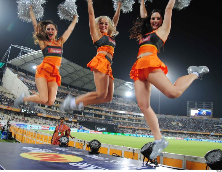 Cheerleaders leaping up high with their pompoms