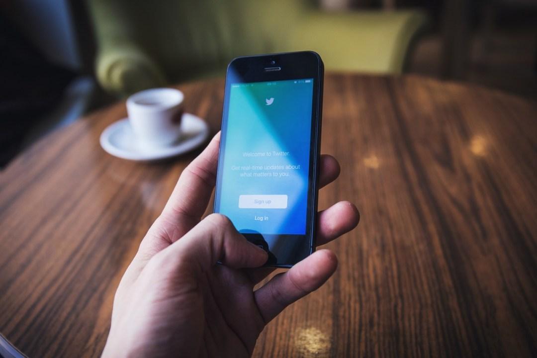 mano sosteniendo smartphone con spp de twitter abierta, en 2017 la optimización móvil será clave en las estrategias de marketing en redes sociales