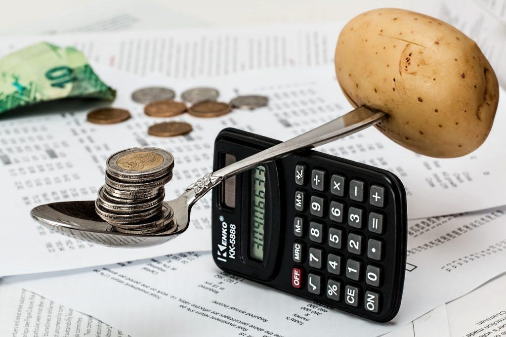 balanza hecha con calculadora, cuchara, monedas y una papa, generar costos de cambio ayuda a fidelizar clientes