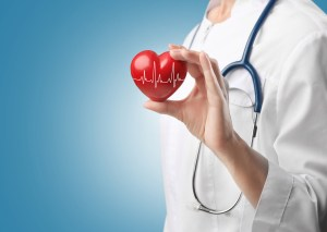 Cardiologist holding red heart with electrocardiogram