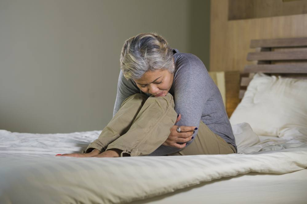 Mature, sad woman sitting on her bed feeling overwhelmed