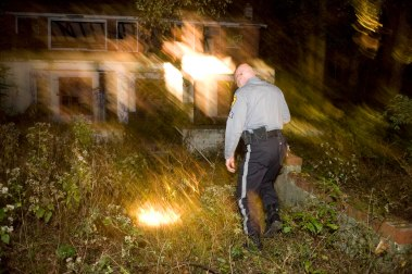 Sgt. Rick Kieft, Burlington County park police, checks out an old abandoned property in Rancocas Park Monday night. Kieft works the overnight shift patroling parks in the Hainesport- Mount Laurel area. Story on working nights. 10/12/09