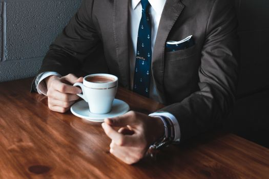 Man in suit drinking coffee.