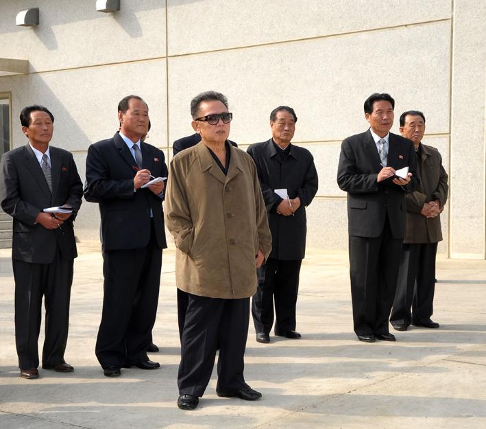 Kim Jong-il at the 26 September Pig Farm.  One may note Gen. Ri Myong-su at the far right without his KPA uniform. (Photo: KCNA)