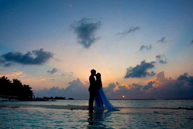 silhouette photo of man and woman kisses between body of water