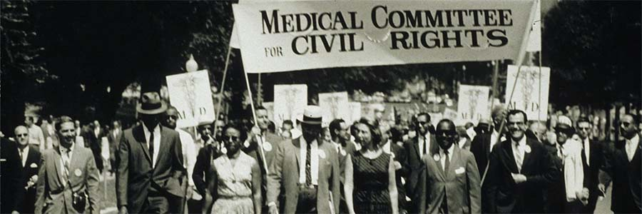 "Men in suits and women in dresses march peacefully down the street under a banner reading """"Medical Committee for Civil Rights"""