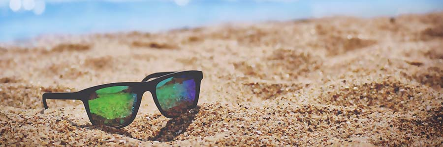 Dark sunglasses perch in the sand, blue water visible just beyond