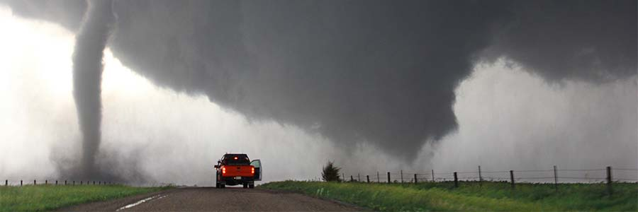 A tornado funnel touches down in a field. A red pickup truck is stopped on the road nearby.