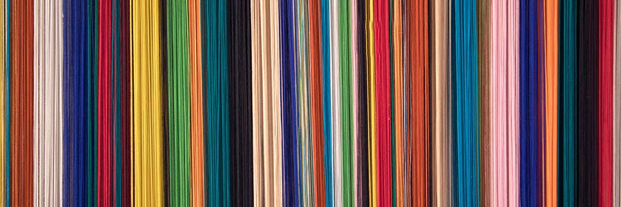 Tight close-up on a threads of different colors lined up