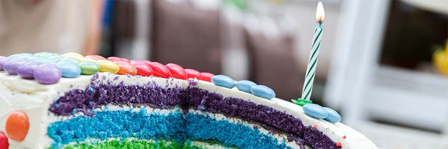 A brightly colored birthday cake with one lit candle on top