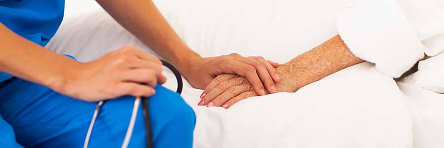 close-up of a nurse holding a patient's hand