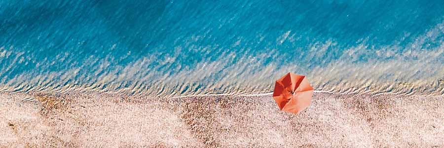 Aerial view of a single red beach umbrella at the line between the blue sea and the light sand