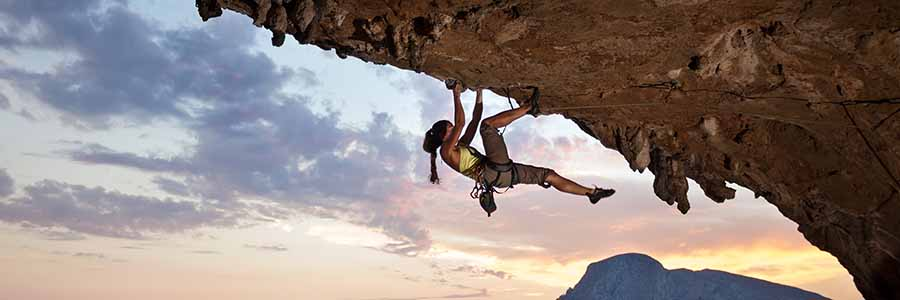 A young female rock climber hangs from the underside of an outcropping