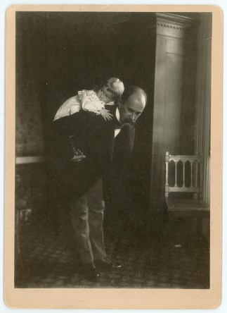 Osler giving his very young child a ride on his back.