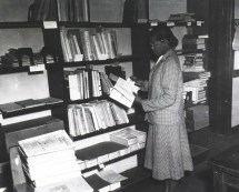 In the processing section Miss Meeds is standing in front of bookshelves comparing a catalog card to the title page of a book.