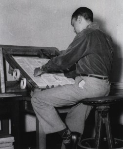 seated at a drafting table a man tapes papers together.
