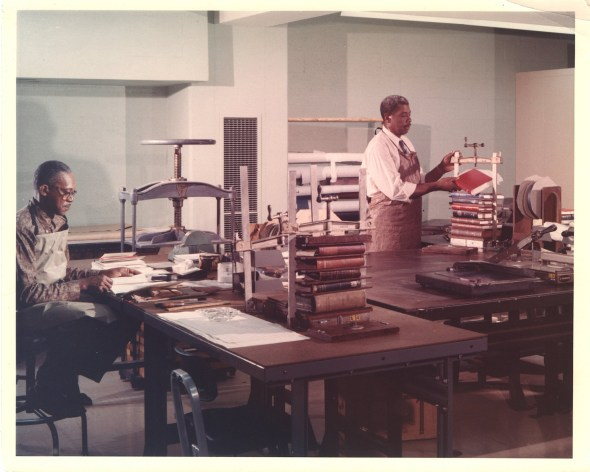 Two men in aprons work at large tables holding tools and bookpresses.