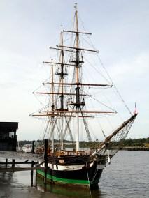 A tall ship of three masts at dock with no sails set.