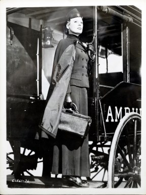 June Allyson in a red cross uniform stands on the step of an ambulance wagon holding a black bag.
